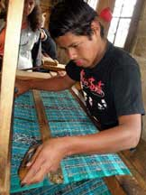 A young man weaves a complex pattern on a floor loom
