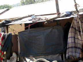 Plastic protecting a makeshift kitchen on the back of a resettlement home