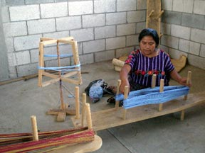 A woman seated on the ground winding a warp in the community center