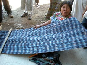 A woman proudly displays the wide jasp fabric she has woven on a backstrap loom