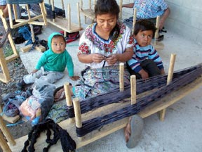 A woman tends her small children while she works on a backstrap warp
