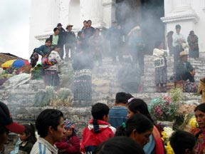 A view of the people on the church steps seen through a cloud on burning incense